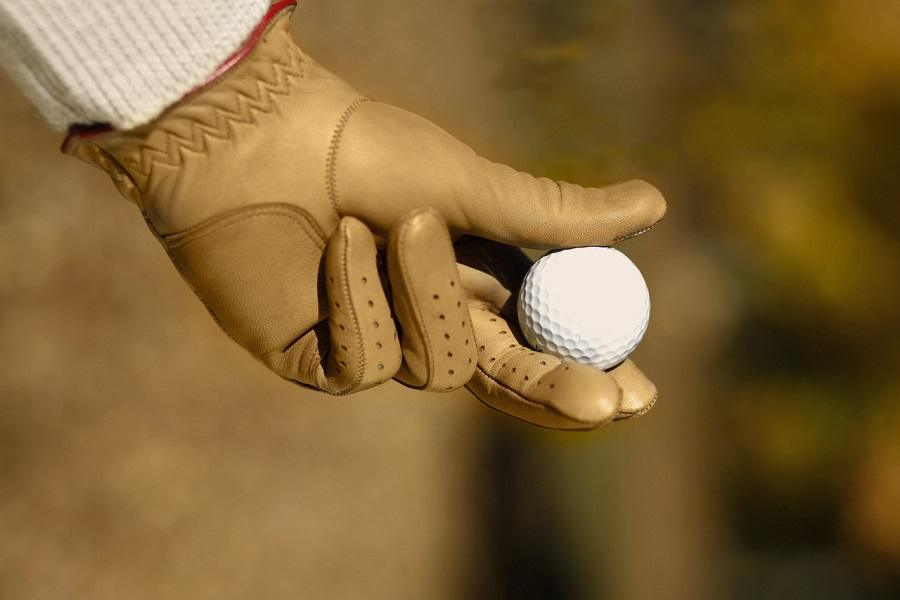 Hand Holding Golf Ball with Vintage Golf Gloves