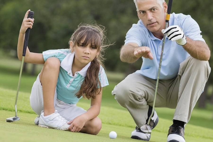 Man Teaching Young Girl a Golf