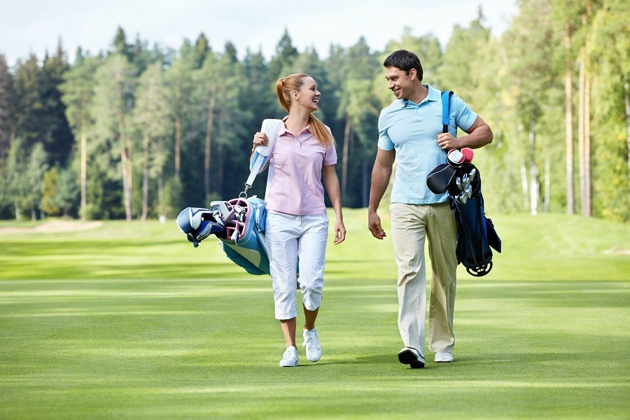 Young Couple Walking on the Golf Course